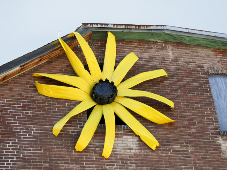 Big flower sculpture on the wall of a building in Evergreen Brick Works Park by Loozrboy